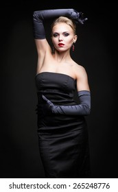 Young blonde woman in black dress and long gloves on dark background
