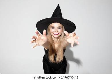 Young blonde woman in black hat and costume on white background. Attractive caucasian female model posing. Halloween, black friday, cyber monday, sales, autumn concept. Copyspace. Looks scary, smiling