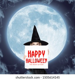 Young blonde woman in black hat and costume. Attractive female model against big moon midnight. Calling for sale. Black friday, cyber monday, sales, autumn concept. Flyer for your ad.
