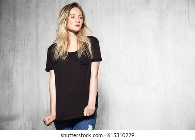 Young blonde woman in a black T-shirt standing on the cement wall background