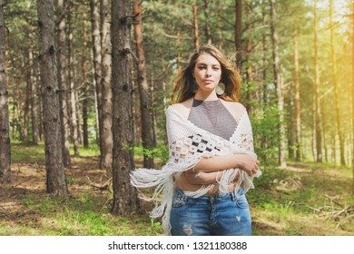Young blonde woman in boho fashion outfit. Bohemian style female person on sunny windy day in park posing. Natural lighting.