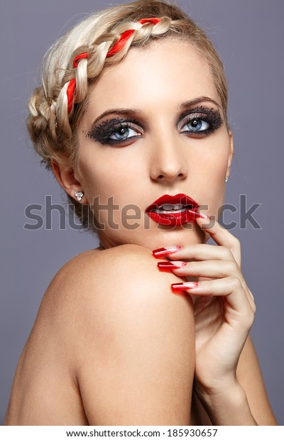 Young blonde woman with braid hairdo and red nails on gray background