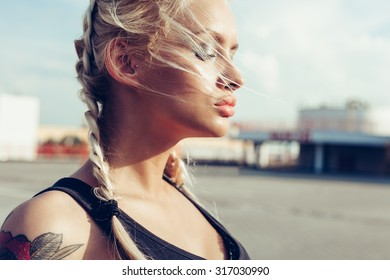 Young blonde woman with braided pigtails. Soft sunny color outdoors portrait.