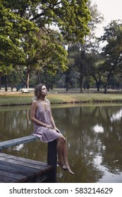 Young blonde woman in casual dress enjoing nature in park near the pond