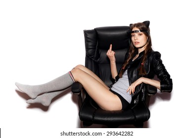 Young blonde woman in cat ears sit on black office chair and show middle finger. Fashion hipster girl.  White background, not isolated
