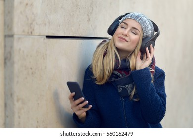 Young blonde woman in coat and hat standing outside against concrete wall holding smart phone in hand with eyes closed smiling listening to music in wireless headphones