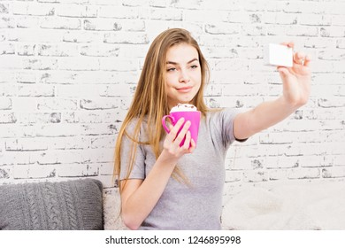 Young blonde woman with coffee smiling and taking a selfie. Studio lighting, no retouch, brick wall background.
