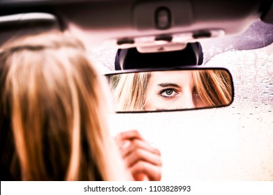 Young blonde woman is correcting her makeup, painting her lips with lipstick in a rear view mirror of her car. Lifestyle conception.