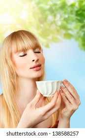 Young blonde woman with cup of herbal tea
