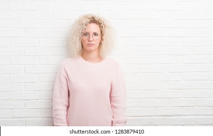 Young blonde woman with curly hair over white brick wall with serious expression on face. Simple and natural looking at the camera.