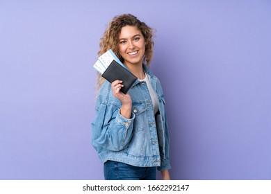 紫の背景に金髪の若い金髪の女性が、旅券と飛行機の切符で幸せに過ごす