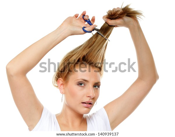 Young blonde woman cutting her hair with scissors - unhappy expression, isolated on white background