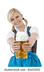 Young blonde woman with dirndl toasts with beer stein.Isolated on white background.