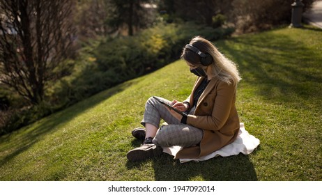 young blonde woman dressed in a beige coat in a black mask sitting on the grass with handsfree or wireless headphones on searching something in the tablet