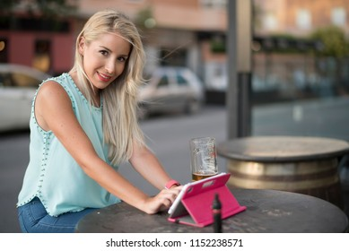Young blonde woman drinking beer in bar and looking tablet in outdoors image