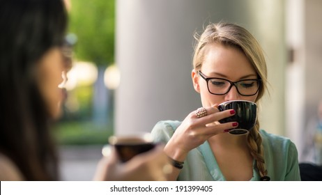 Young blonde woman drinking coffee with friend in a cafe outdoors. Shallow depth of field.