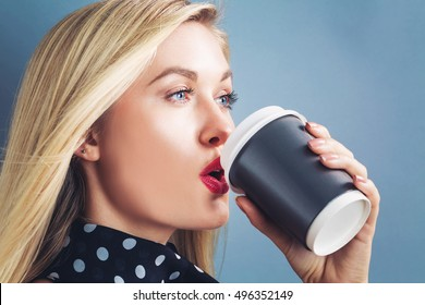 Young blonde woman drinking coffee on a gray background