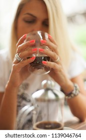 Young blonde woman drinking and looking at glass of coffee