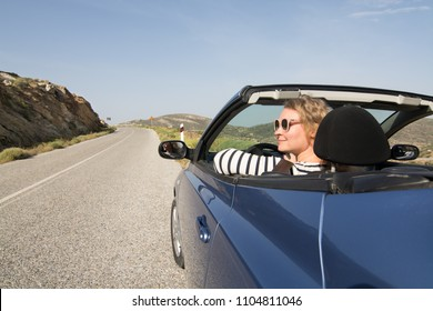 Young blonde woman driving in convertible blue car without roof on mountain road in Naxos island, Greece. Wide angle lens shot.