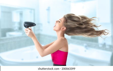 Young blonde woman drying her long hair with electric fan