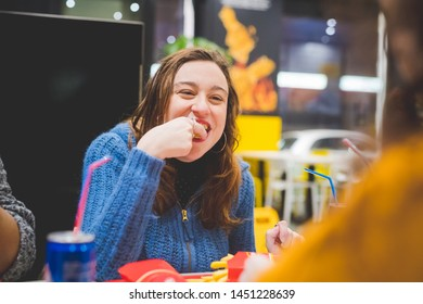 young blonde woman eating in fast food with friends– hungry, conviviality, sharing