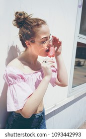 Young blonde woman eating an strawberry ice cream