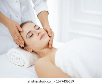 Young and blonde woman enjoying facial massage in spa salon. Beauty concept