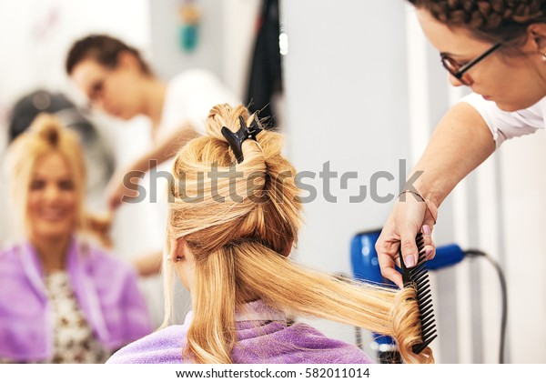 Young blonde woman enjoying hair treatment.