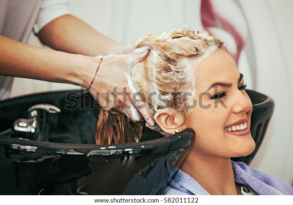 Young blonde woman enjoying hair treatment.
