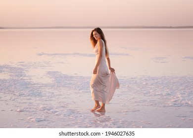 Young blonde woman in an evening airy pastel pink, powdery dress stands barefoot on white crystallized salt. Girl with natural make-up, hair is developing. Salt mining trip, walking on water at sunset
