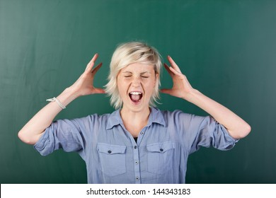 Young blonde woman with eyes closed shouting in front of chalkboard