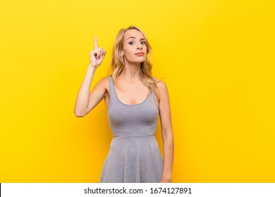 young blonde woman feeling like a genius holding finger proudly up in the air after realizing a great idea, saying eureka against orange wall