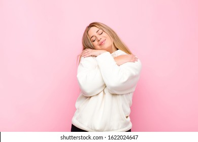 young blonde woman feeling in love, smiling, cuddling and hugging self, staying single, being selfish and egocentric against flat wall