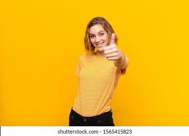 young blonde woman feeling proud, carefree, confident and happy, smiling positively with thumbs up against flat color wall