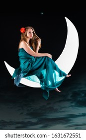Young blonde woman with a flower bud in her hair sit on the moon hanging over dark clouds