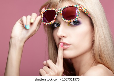Young blonde woman with fun candy glasses on pink background. Portrait of female with finger on lips