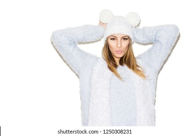 Young blonde woman in fuzzy sweater, knitted white hat with pom poms and scarf. Studio lighting, no retouch, isolated on white background.