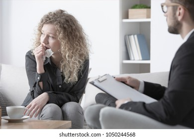 Young, blonde woman having an emotional breakdown and crying during psychotherapy