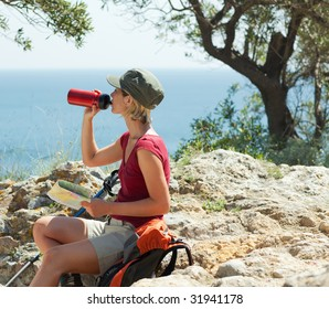 young blonde woman hiking sitting on a rock and drinking water.