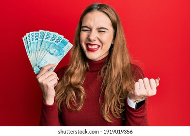 Young blonde woman holding 100 brazilian real banknotes screaming proud, celebrating victory and success very excited with raised arm