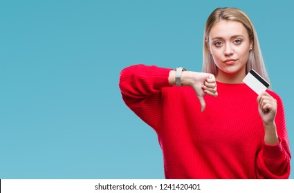 Young blonde woman holding credit card over isolated background with angry face, negative sign showing dislike with thumbs down, rejection concept