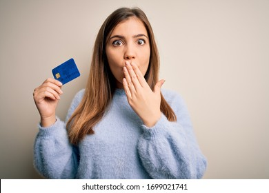 Young blonde woman holding credit card as payment over isolated background cover mouth with hand shocked with shame for mistake, expression of fear, scared in silence, secret concept
