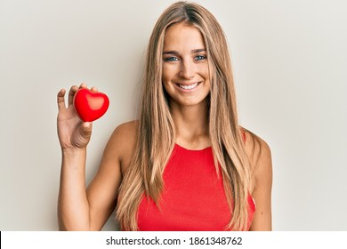 Young blonde woman holding heart looking positive and happy standing and smiling with a confident smile showing teeth