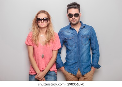 Young blonde woman holding her hands crossed while her lover is holding his hands in pockets.
