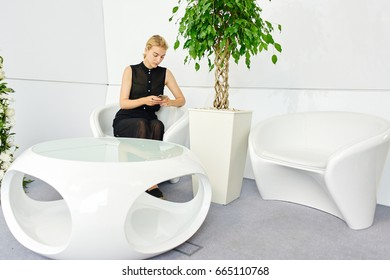 Young blonde woman holding a mobile phone and looks at him sitting in the indoors with futuristic white furniture