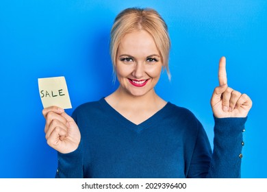 Young blonde woman holding sale word reminder smiling with an idea or question pointing finger with happy face, number one
