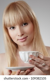 Young blonde woman holding tea or coffee cup