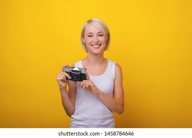 A young blonde woman, holding a vintage camera and trying to take a photo