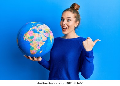 Young blonde woman holding world ball pointing thumb up to the side smiling happy with open mouth