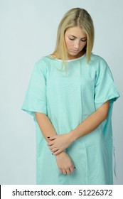 Young blonde woman in hospital gown looking down dejectedly